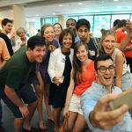 Zack Newbauer '15, who recently returned from Australia, takes a selfie with Chancellor Carol Folt and international students and returning UNC study abroad students.