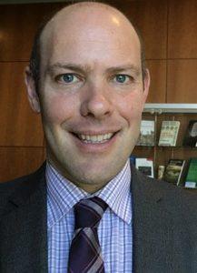 Headshot of Alex Frigo wearing suit and smiling