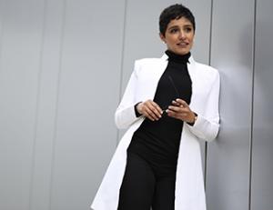 Nourah Shuaibi leaning against wall wearing long white jacket