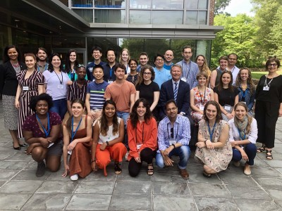 Group of 30 people posing together for a photo outside of the Global Education Center