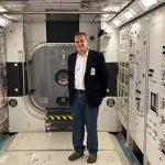 Man standing near scientific equipment.