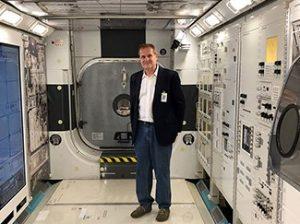 Stephan Moll standing near scientific space equipment.