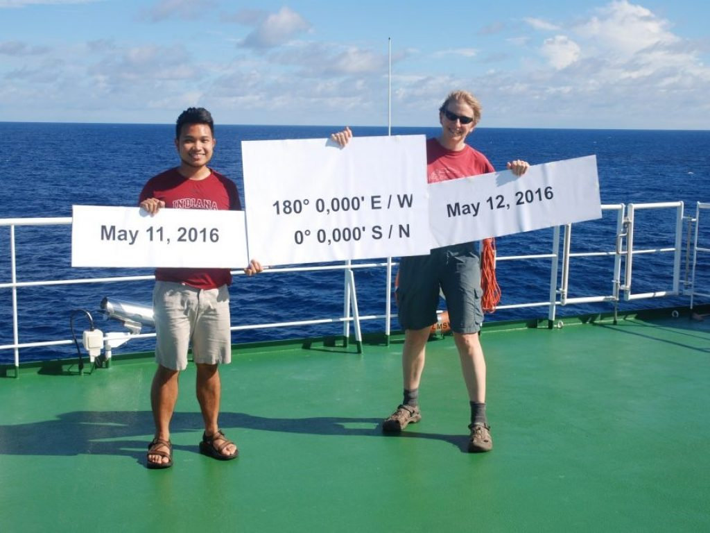 John Paul Balmonte '17 Ph.D. with another student on boat holding up sign with equator coordinates