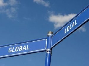 Intersecting street signs that read Global and Local