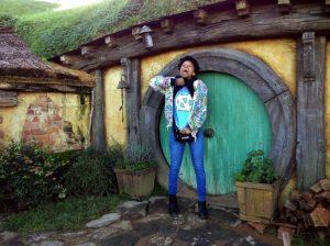 Head shot of Krista McGuire '16 showing off UNC t-shirt in front of Hobbit portal in New Zealand