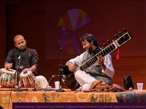 Two men sitting on a stage and playing instruments