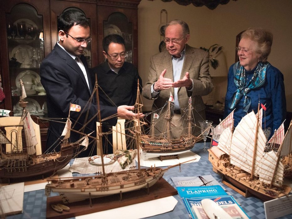 Four people around a table looking at ship models