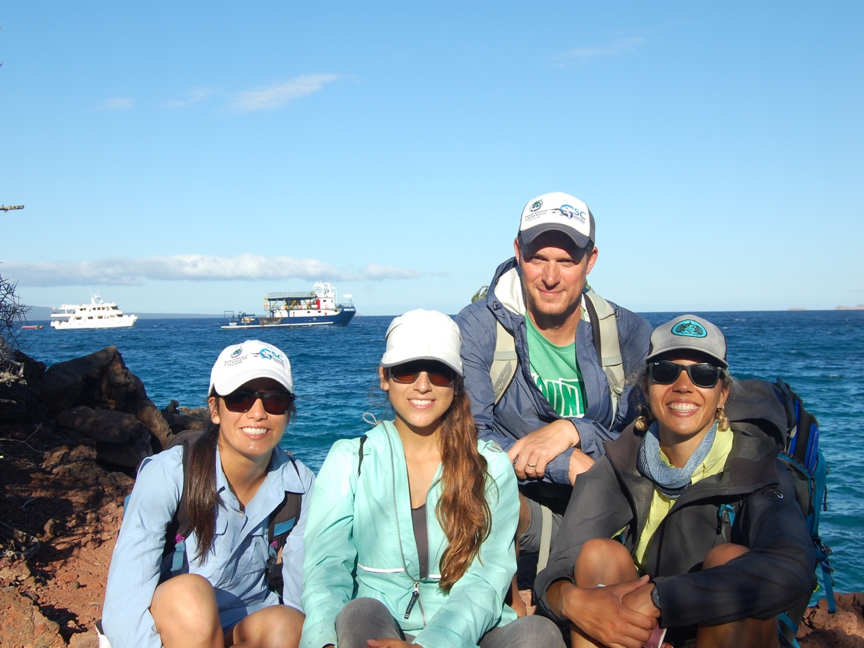 Four people sitting and posing outside in front of an ocean