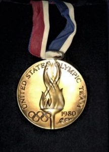 """Gold toned medal that states"""" United States Olympic Team"""" around edge with Olympic rings, flames and 1980."""