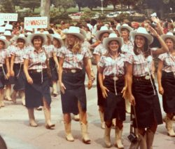 Parade of women wearing navy knee length skirts and white blouses and hats
