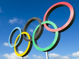 Olympic rings (five interlocking circles) with blue sky background