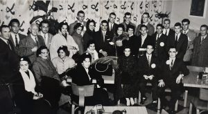 Black and white photo shows about 28 people. Mainly men are in the back and women in the front.