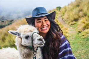 A student poses with an alpaca on a hillside in Quito, the capital of Ecuador. The girl is smiling wide and there are gray skies in the background.