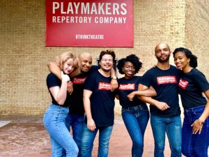 Group of students stand in front of Playmakers Repertory Company sign