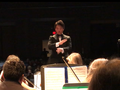 View of orchestra conductor from back row of string players seated and playing.