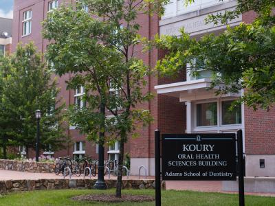 Exterior of brick building with sign: Koury Oral Health Sciences Building - Adams School of Dentistry.