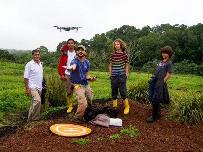 Group of people in field watching drone.