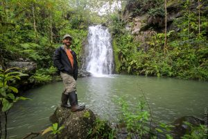 Francisco stands in front of waterfall.