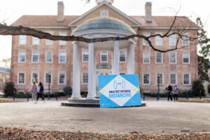 """Students walk past the Old Well. The image is focused on a signage that says """"practice physical distancing"""""""