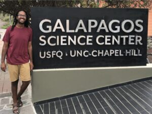 Khristopher poses next to building sign.