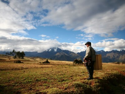 Man with painting supplies looks out over pasture landscape with mountains in the background.