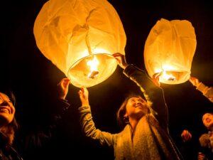Students hold lit paper lanterns towards dark sky