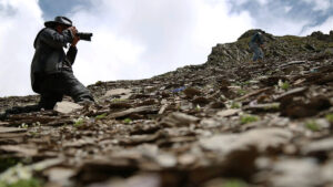Person crouched photographing mountainside
