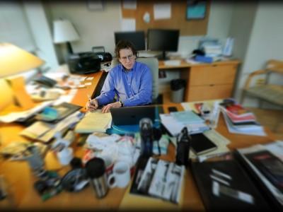 Adam Versényi sits at desk