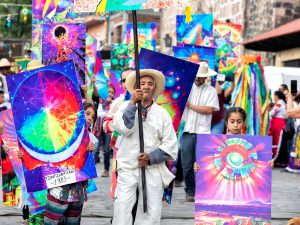 Parade of people hold colorful artwork in streets