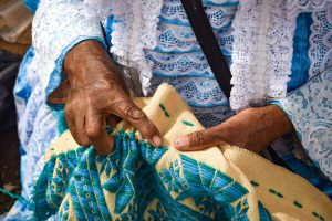 Woman's hands works with beige textile embroidered with green and blue threads.