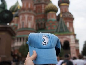 A hand holding up a Carolina blue baseball cap with a logo of a tar heel in the center. In the background, St. Basil's Cathedral, a building with many colorful, onion-like domes.