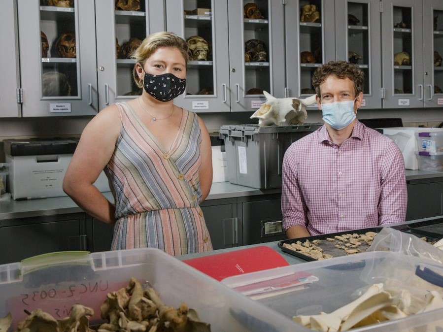 Masked student and professor in lab with artifacts