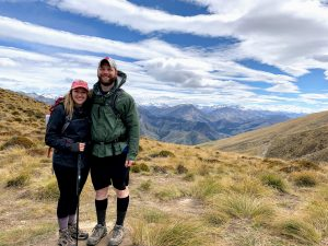 Katelyn Brown-Gomez (right) with her husband John (left) in New Zealand. They are standing on dry grass in front of a mountain scape. They are wearing hiking gear. Brown-Gomez is holding a hiking stick.