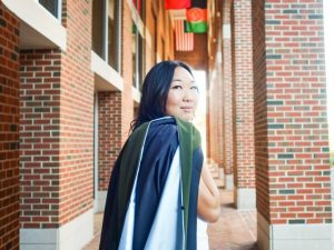 Grace Yook at McColl Building at the Kenan-Flagler Business School. She is holding her graduation gown and stole draped over her right shoulder.