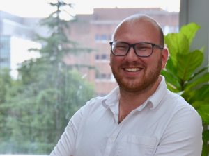 Headshot of Kittner. He wears black, rectangular glasses and a white polo shirt. There is a fiddle leaf plant behind him.