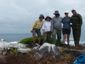 Five scientists stand together, shoulder to shoulder, on a rock in front of the ocean. The sky is cloudy and gray. A white bird stands near them to the left.