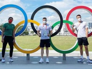 Olympians stand in front on Olympic rings
