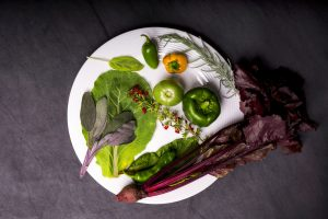 Leafy greens and green bell peppers on a white plate.