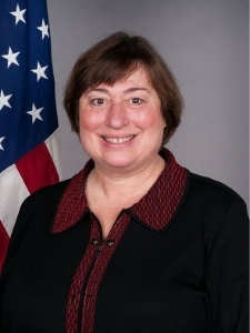 Headshot of Novelli. She has short brown hair and is wearing a maroon shirt under a black blazer. There is an American flag behind her.