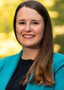Headshot of Ionana Costant. She is wearing a blue-green blazer over a plain black shirt.