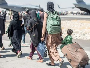 People outside walking to an airplane. They are carrying luggage. One small child sits on a suitcase while his mother pulls it.