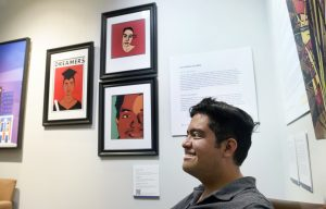 Three framed graphic design works of art. There is paneled text describing the art next to it on the wall .Alanís is sitting in front of it, but you can only see his head.