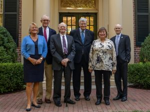 The panelists described in the caption standing together in a line at the front entrance of the Carolina Inn.
