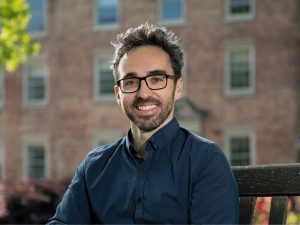 Sáenz sitting on a bench outside. He wears black rectangular frame glasses.