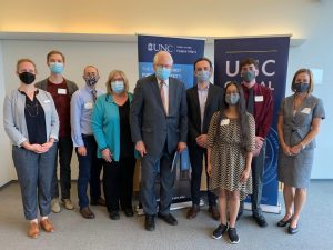 A group of people standing indoors. Everyone is wearing a face mask.